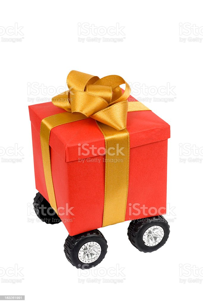 Red gift box with gold  ribbon on wheels stock photo