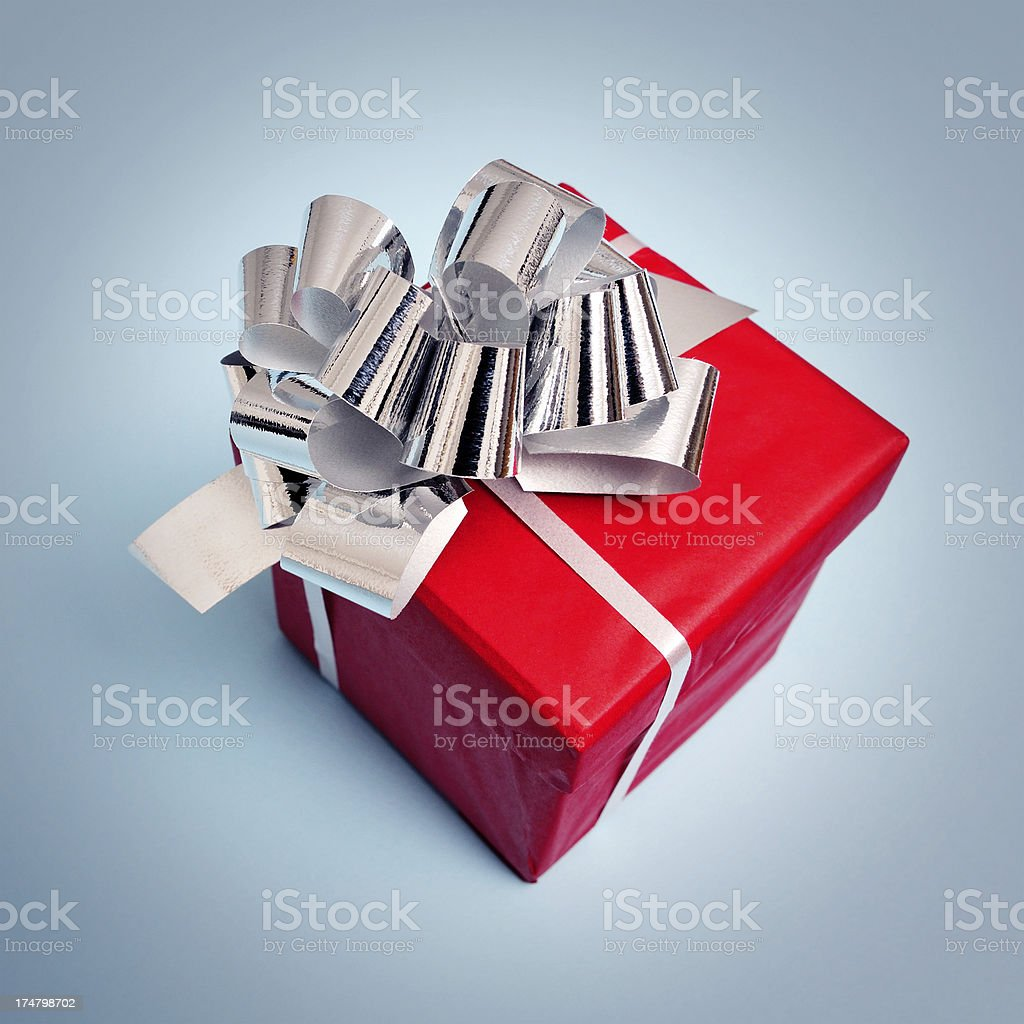 Red gift box with silver ribbon, isolated on blue royalty-free stock photo