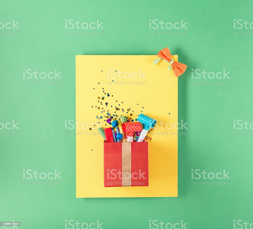 Red gift box with various party confetti, balloons, streamers, n stock photo