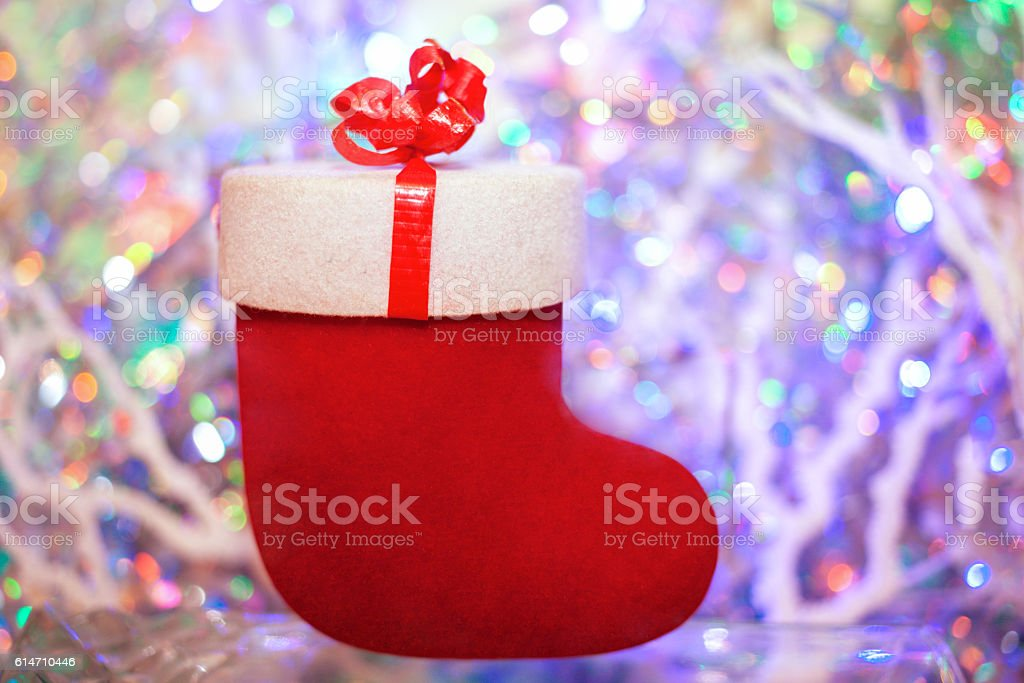Red gift felt boot on a colored background with bokeh. stock photo