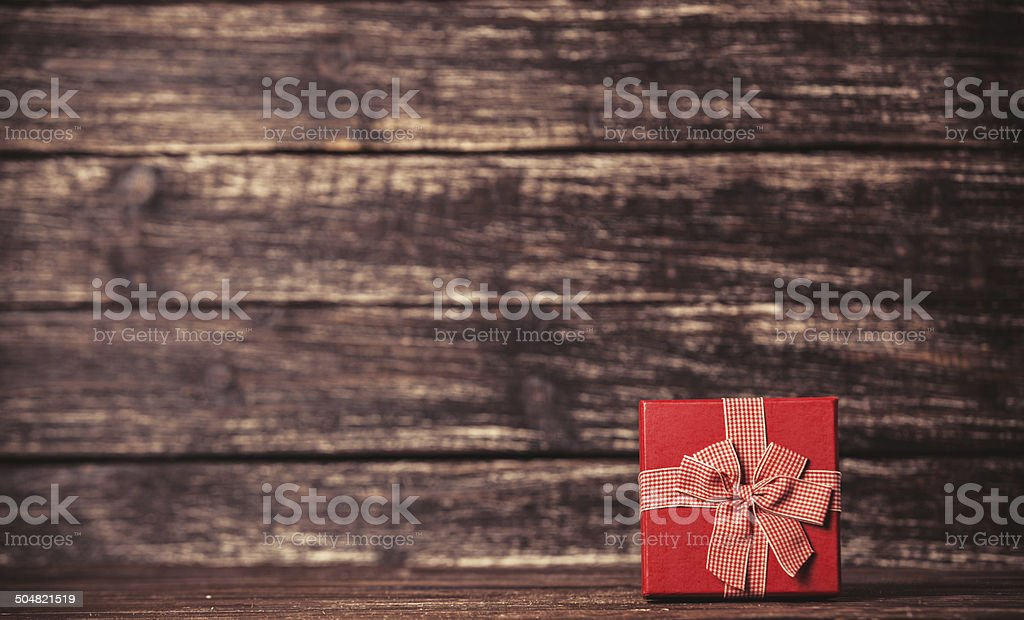 Red gift on wooden table. stock photo
