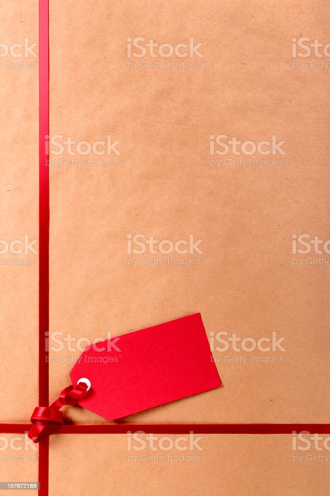 A red gift tag on a red ribbon tied to a package stock photo