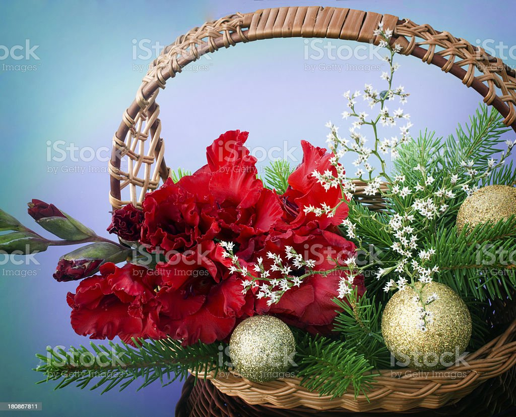 red gladiolus, golden balls are in a wicker basket royalty-free stock photo