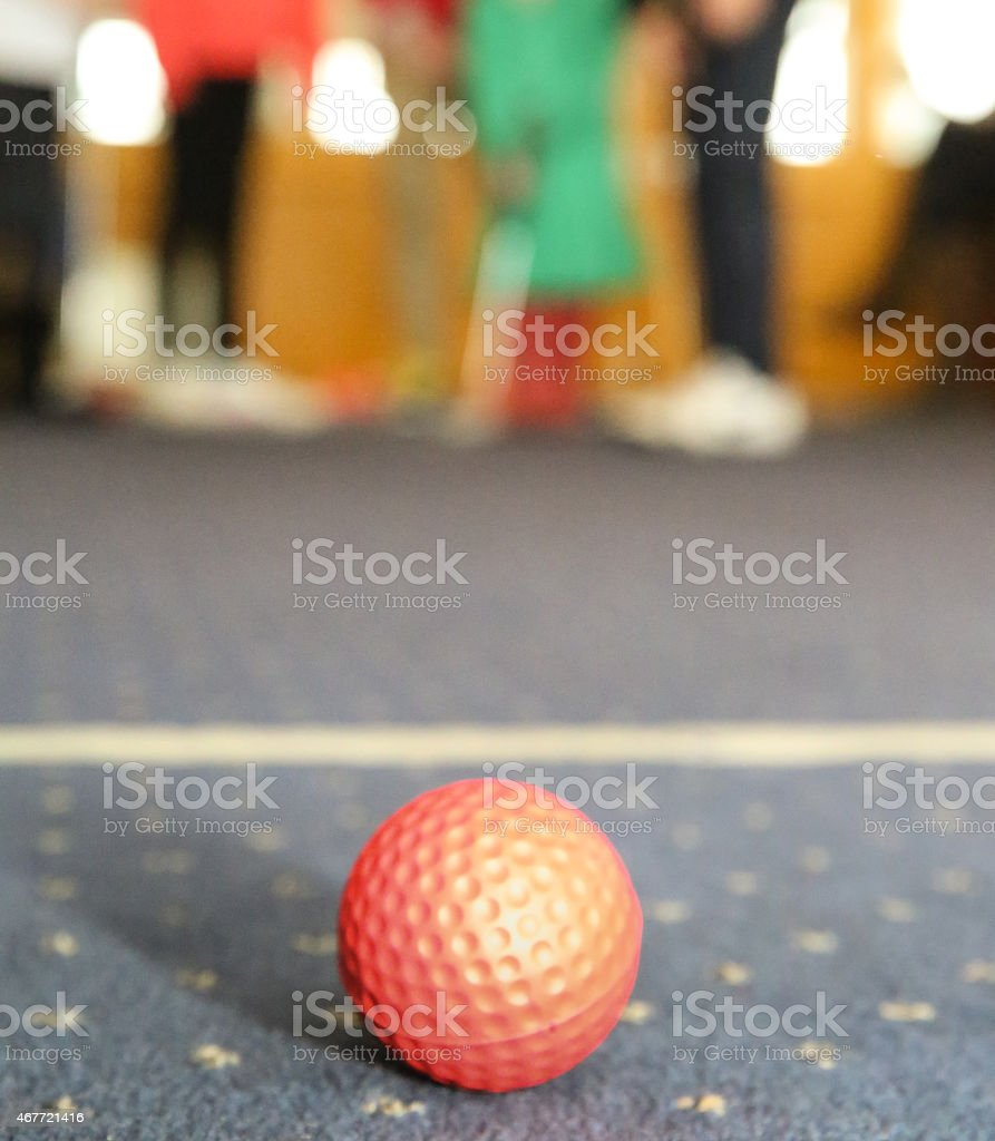 Red golf ball stationary on a carpet - indoor game stock photo