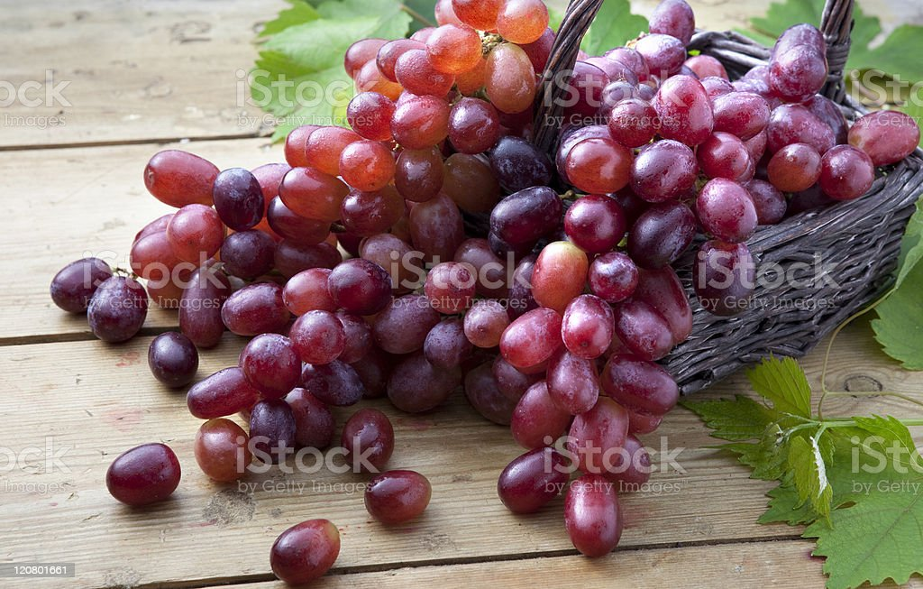 Red grapes in braided basket on wooden table stock photo