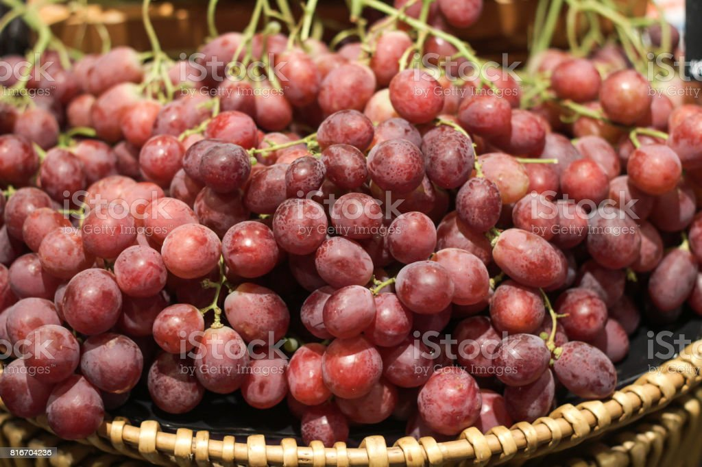 Red grapes in the basket for selling stock photo