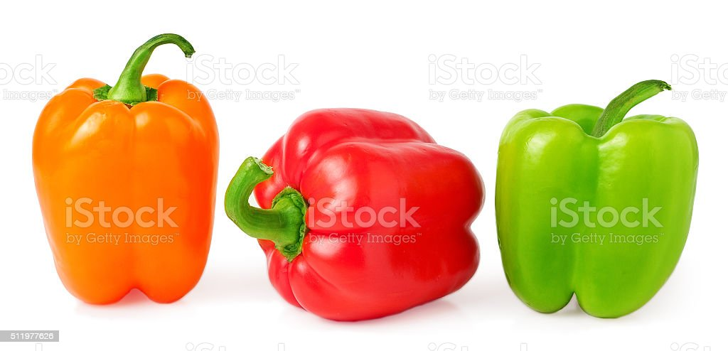 red, green and orange bell peppers on a white background stock photo