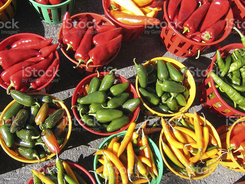Red, green and yellow peppers in baskets stock photo