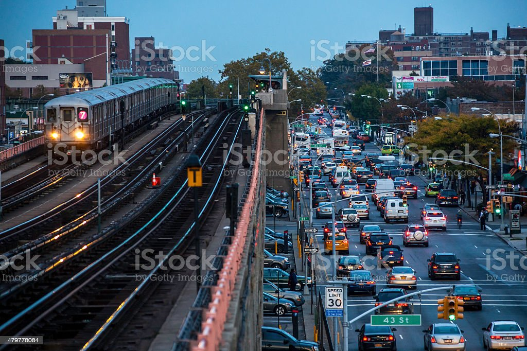 Red, green lights: NYC metro train with traffic at dusk stock photo