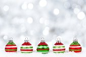 Red, green, white Christmas ornaments in snow with twinkling background
