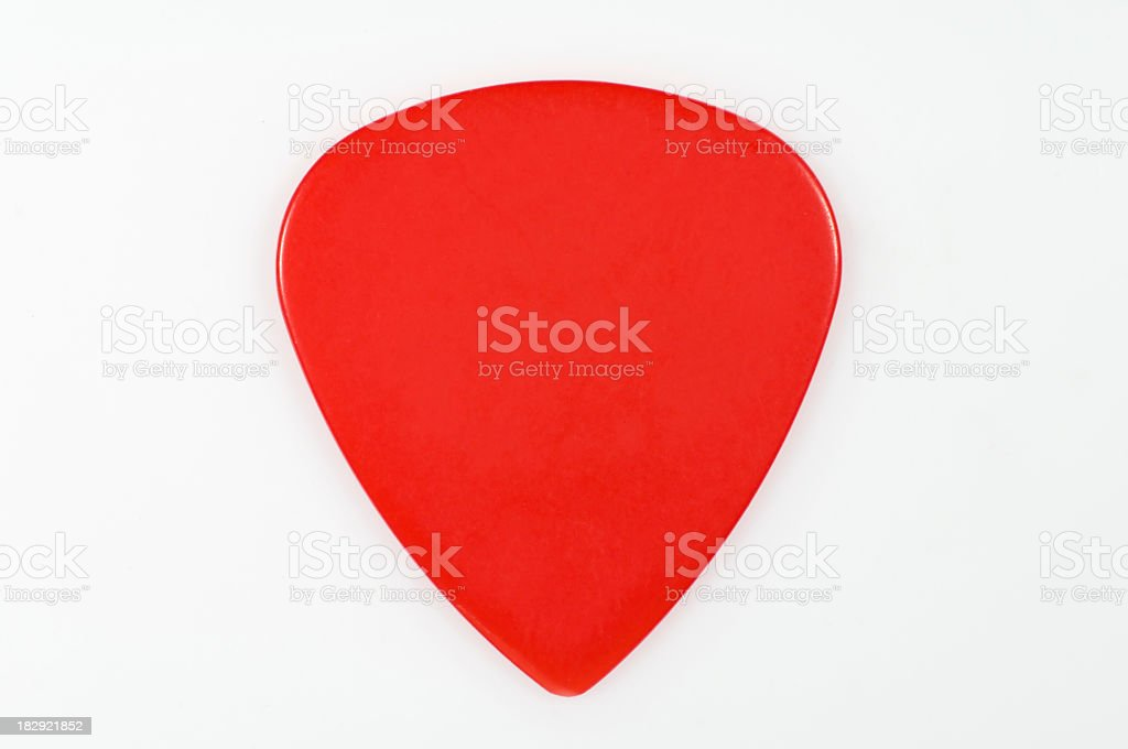 A red guitar pick on a white background stock photo