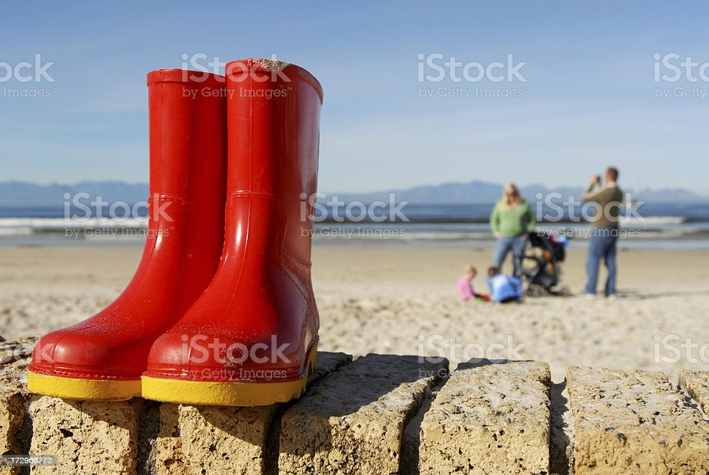 Red gumboots next to the beach royalty-free stock photo