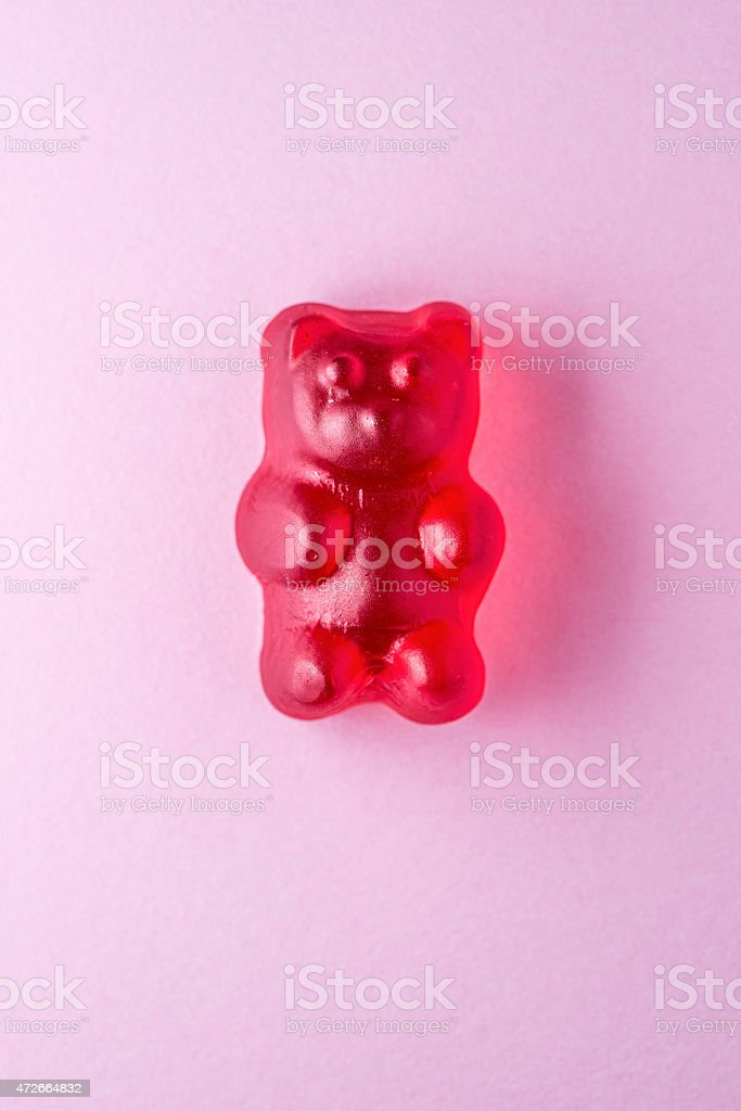 Red gummy bear candy on pink paper stock photo