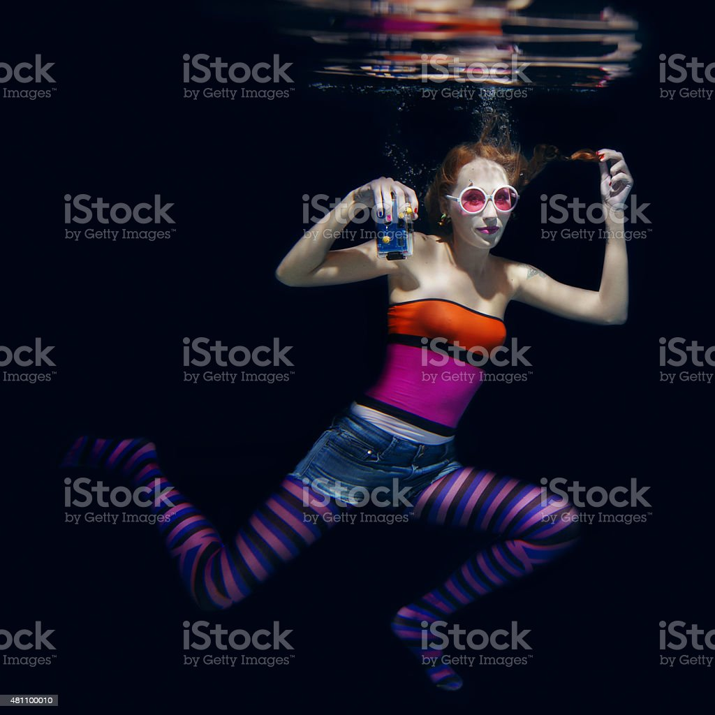 Red hair funny girl on the dark background underwater stock photo