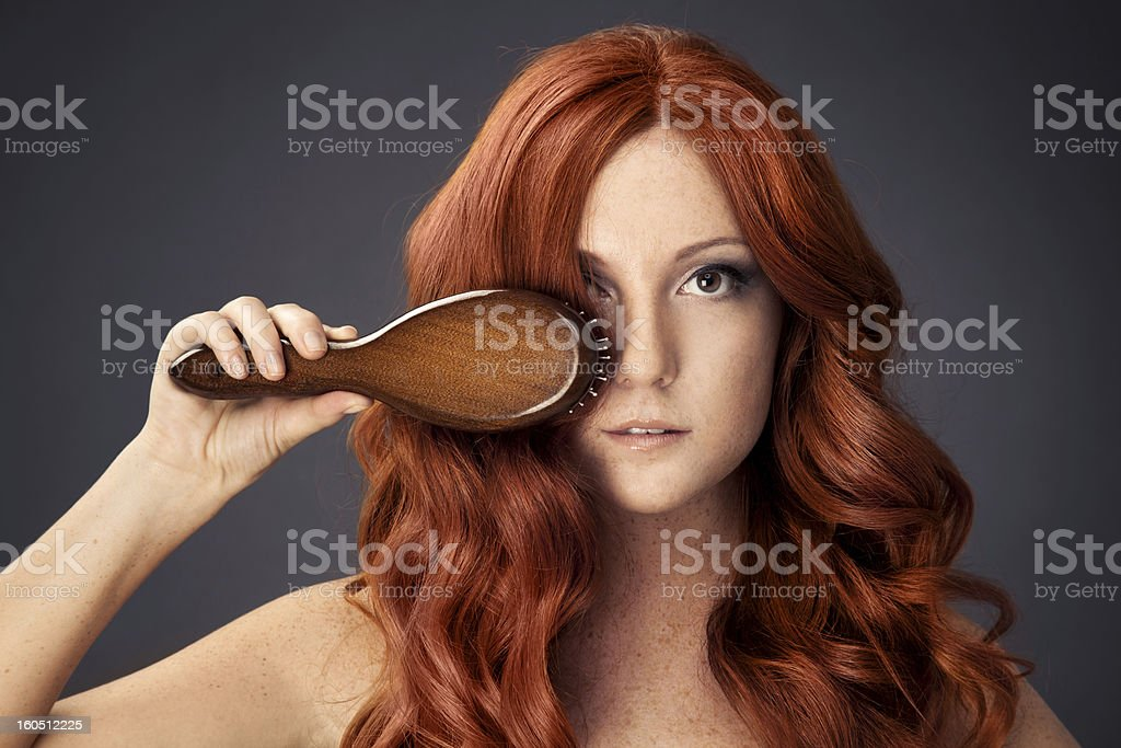 Red hair woman holding a hair brush stock photo