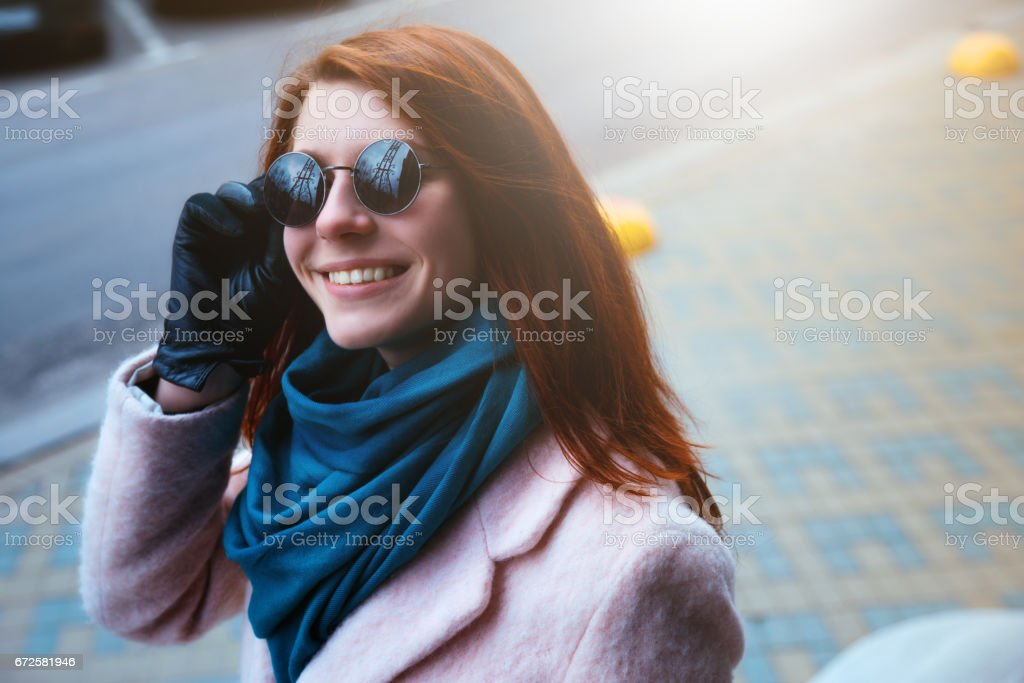 Red haired beautiful girl is walking by the street in a pink coat and blue scarf, with sunglasses. stock photo