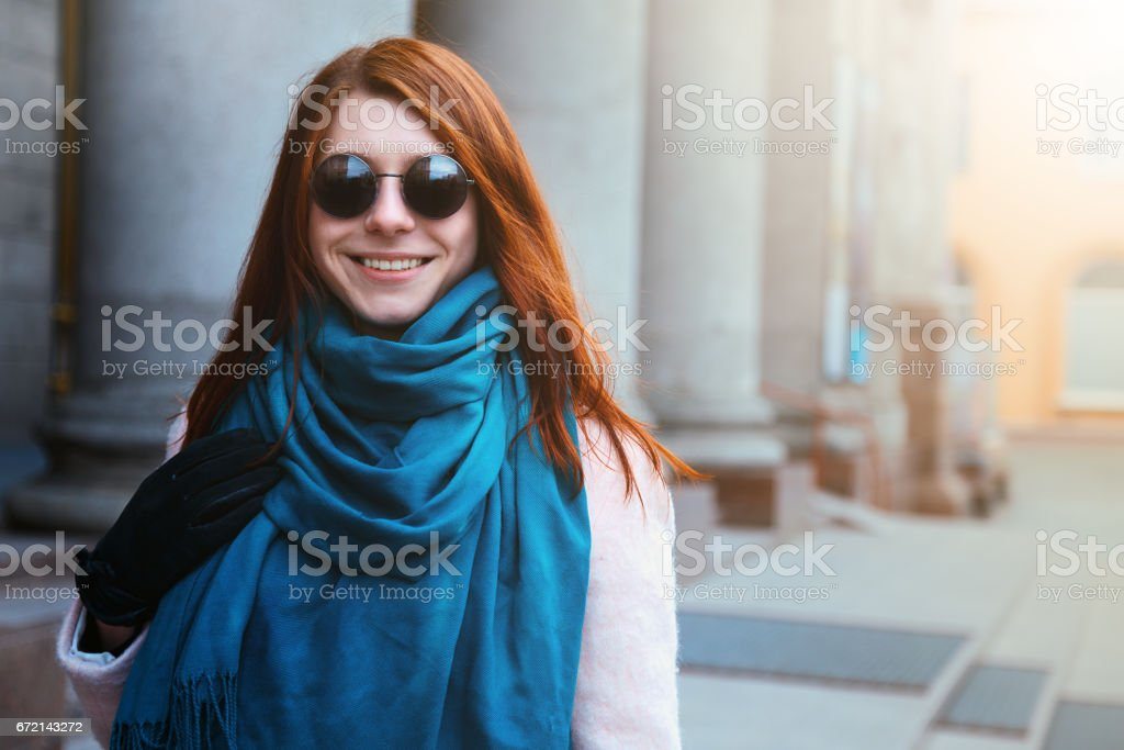 Red haired beautiful girl is walking in the urban background in a pink coat and blue scarf, with sunglasses. stock photo
