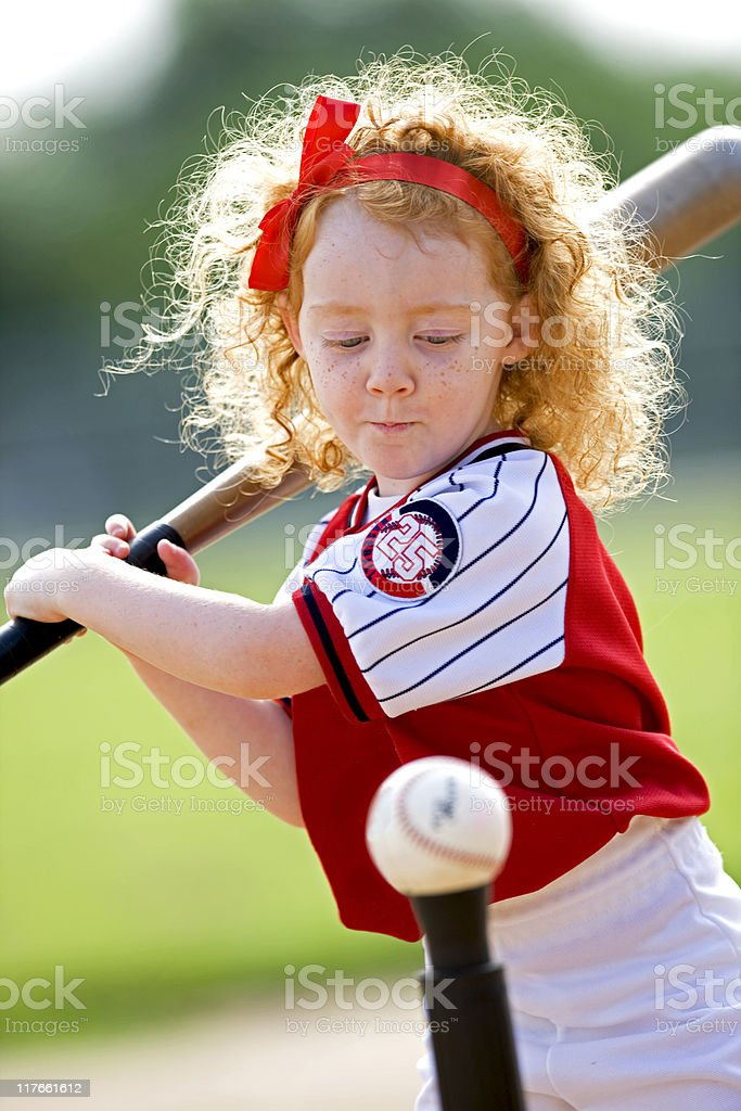Red Haired Girl Hitting Baseball stock photo
