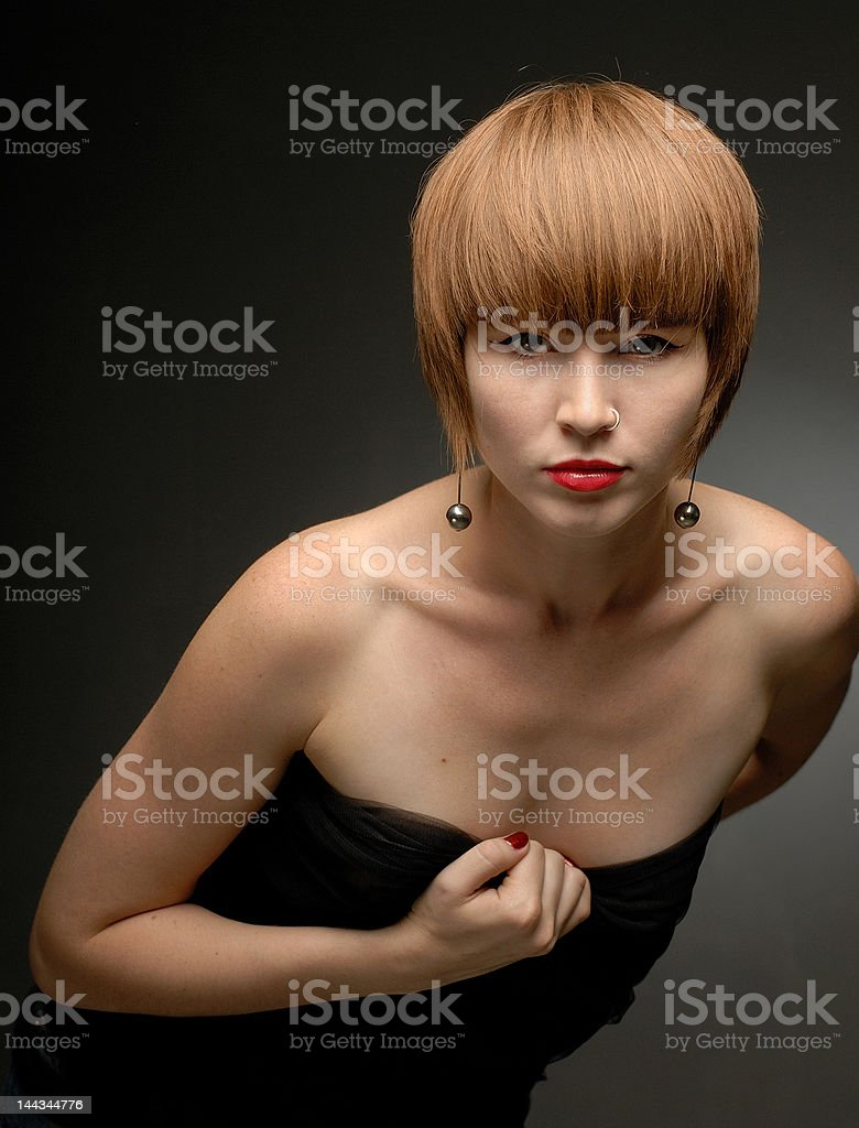 Red haired girl posing leaning forward looking straight royalty-free stock photo
