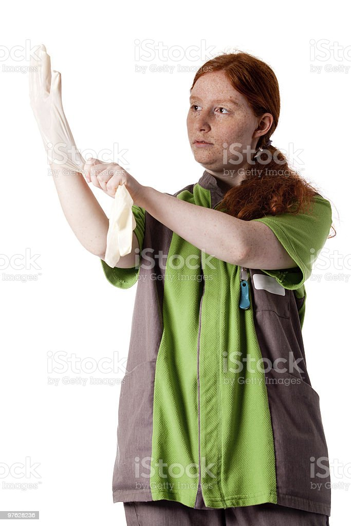 Red haired health care taker putting on her gloves royalty-free stock photo
