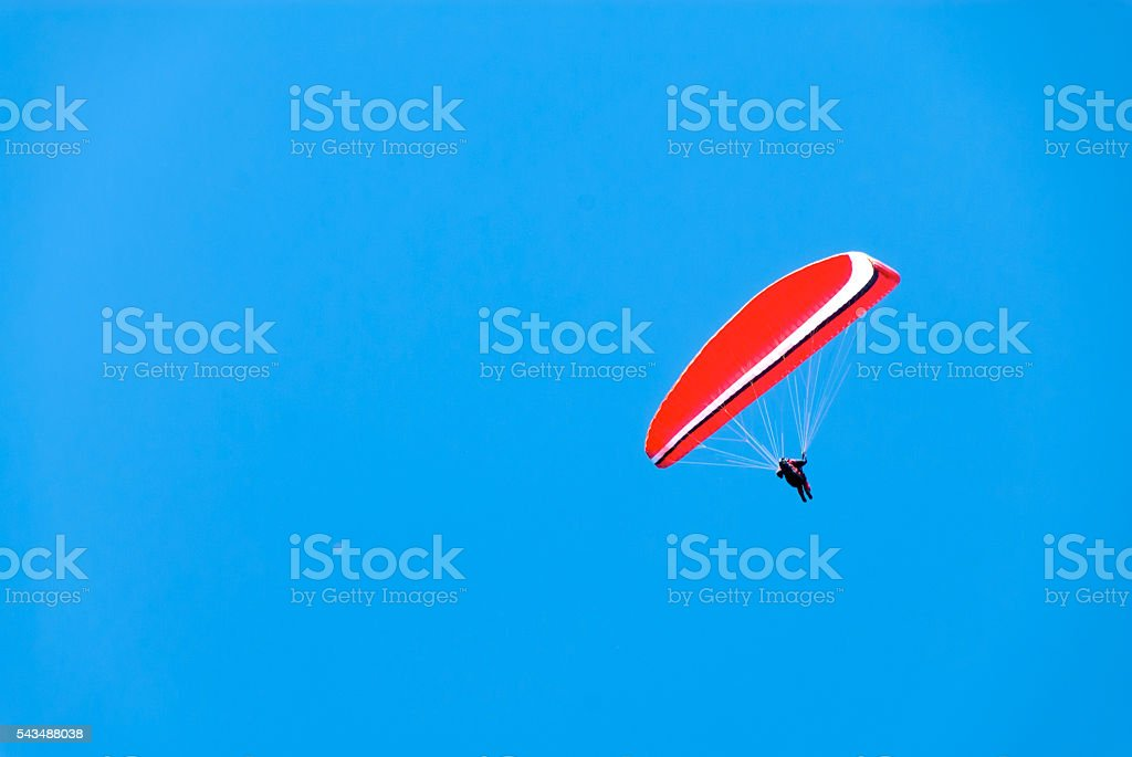Red Hang Glider in a Deep Blue Sky stock photo