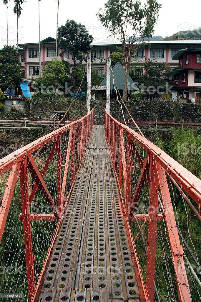 Rosso Hanging Bridge Crossing di Banaue, Filippine foto stock royalty-free