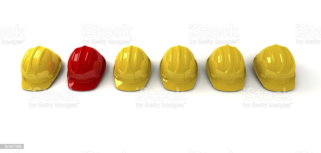 Red hardhat among yellow ones royalty-free stock photo