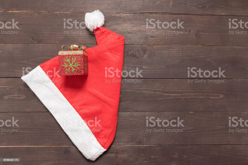 Red hat and gift box are on the wooden background stock photo