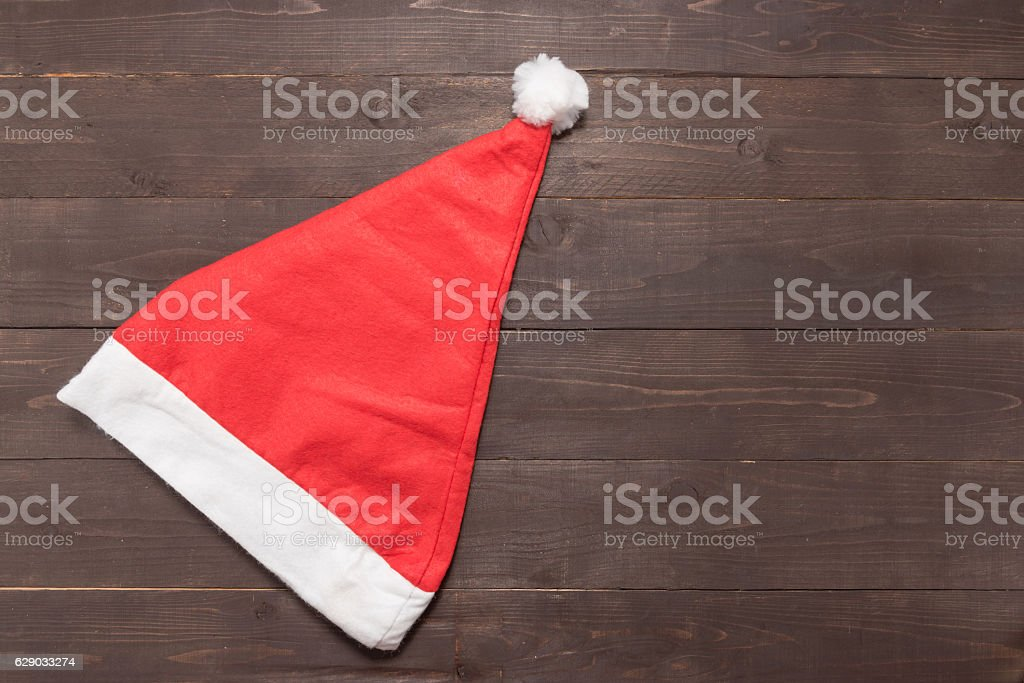 Red hat is on the wooden background with empty space stock photo