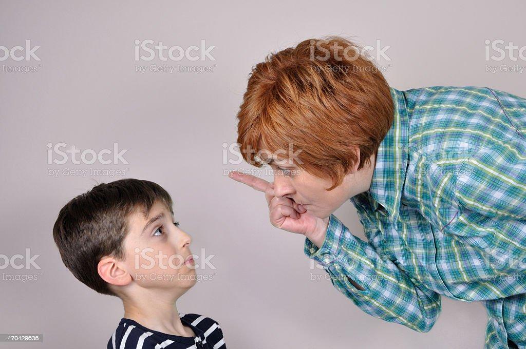 Red head woman scolding a brunette boy stock photo