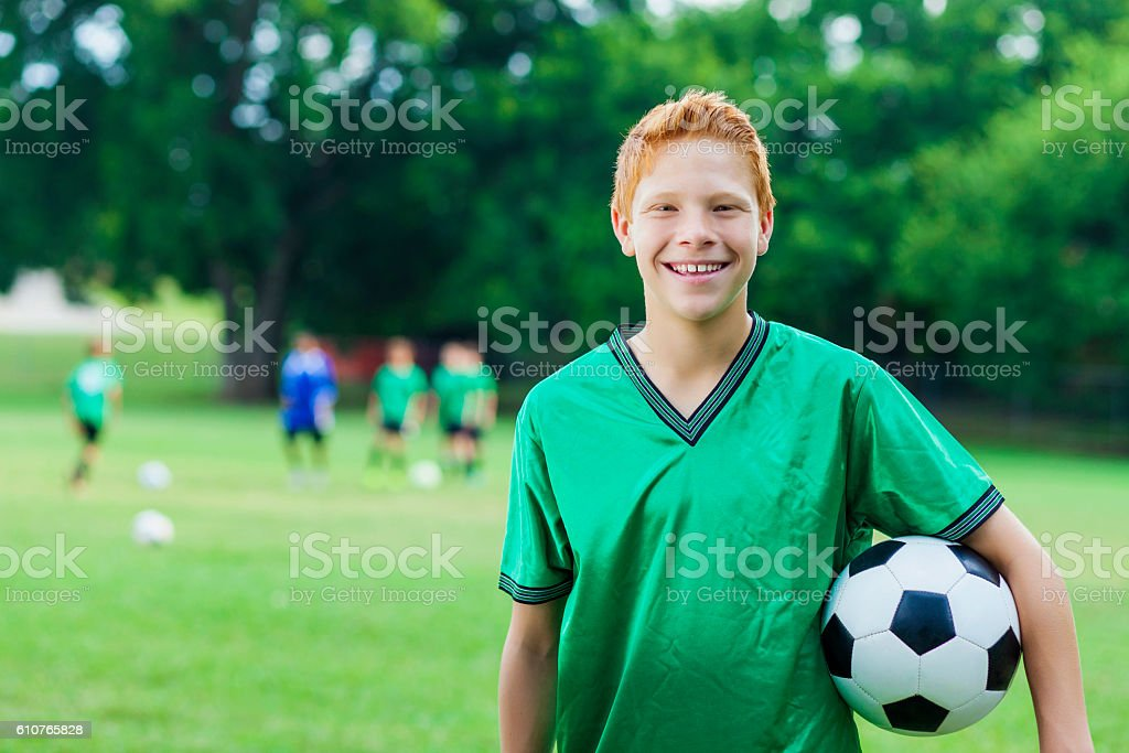 Red headed athlete with soccer ball stock photo