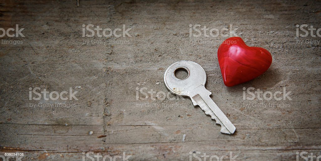 Red heart and a key on rustic wood, love concept stock photo