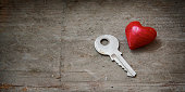 Red heart and a key on rustic wood, love concept