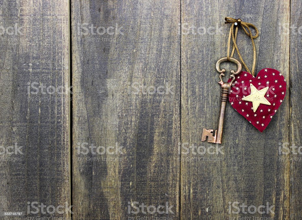 Red heart and key hanging on wooden background stock photo