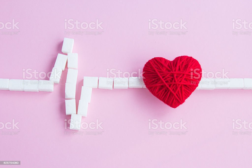 Red heart and sugar cubes heartbeat on a pink background stock photo