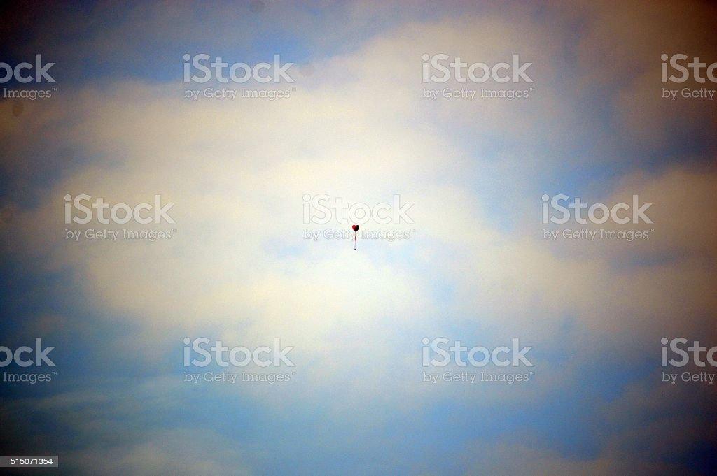 Ballon coeur rouge flottant dans le ciel bleu photo libre de droits