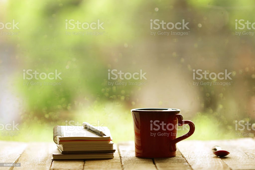 Red heart mug shaped and notebooks at windows stock photo