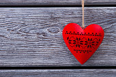Red heart on a wooden fence with space for text.