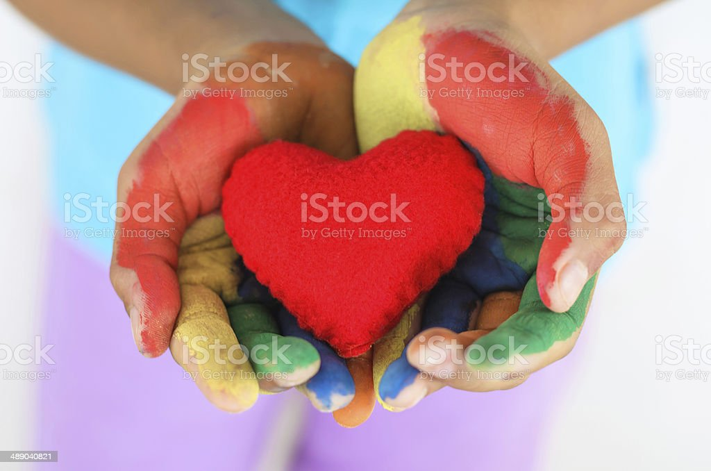 red heart on hand multi color little girl stock photo