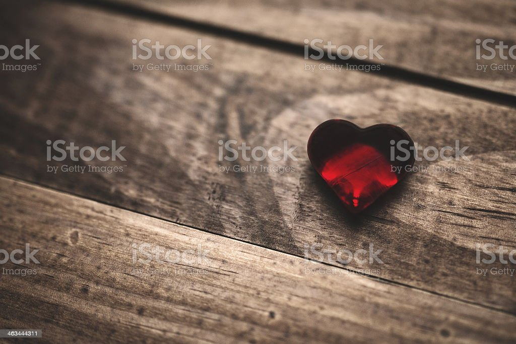 Red heart shape gem on plank for st. valentine stock photo