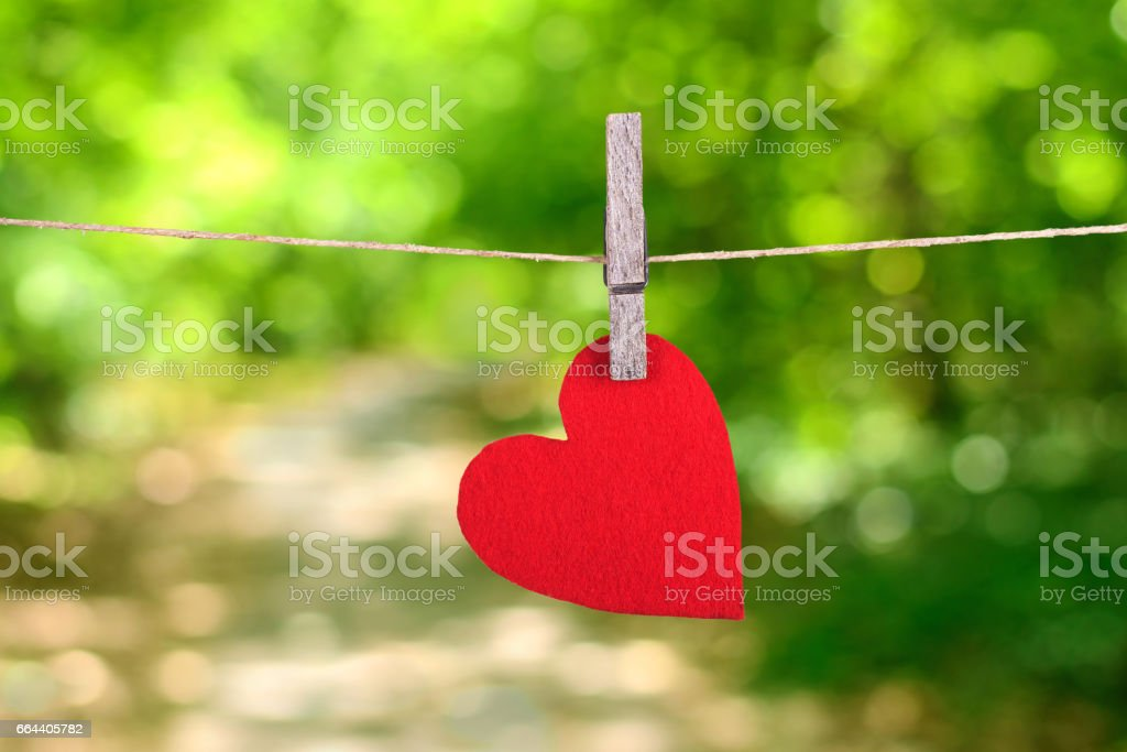 Red heart shape hanging, over the natural background stock photo