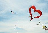 Red heart shape kite is flying in blue sky