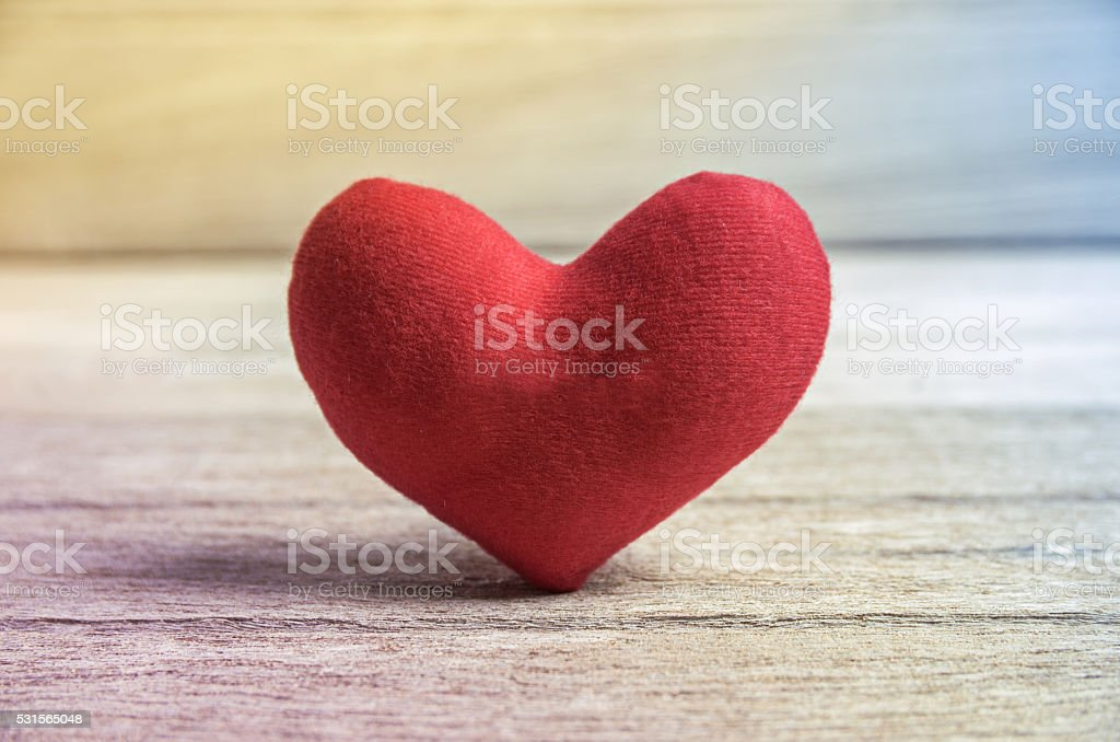 red heart shape on wood background stock photo