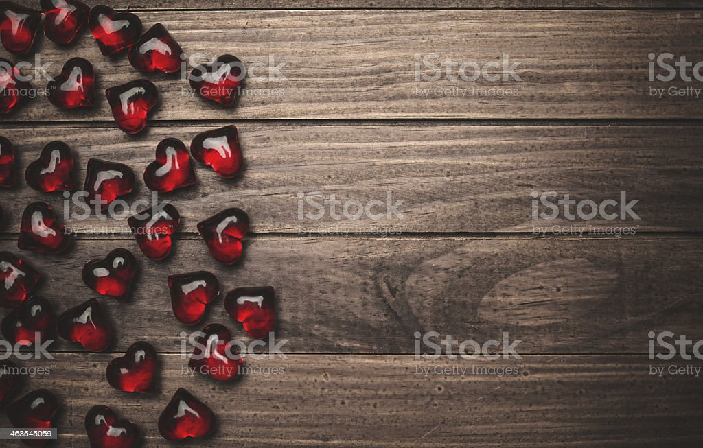 Red heart shape ruby gems on plank for st. valentine stock photo