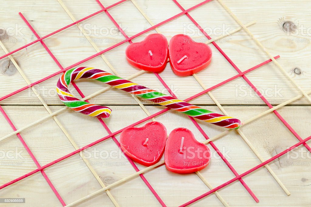 Red heart shaped candles and a candy cane royalty-free stock photo