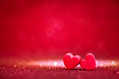 red Heart shapes on abstract light glitter background