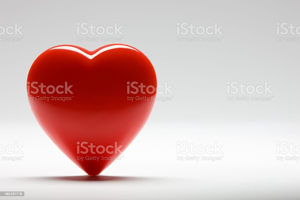 Red heart sitting upright against a white background stock photo