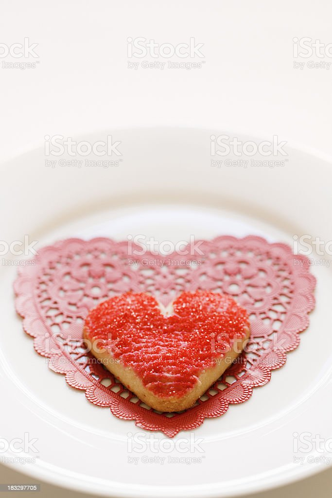 Red Heart Sugar Frosted Valentine's Day Cookie on Lace Doily royalty-free stock photo