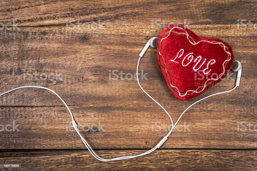 red heart & white earphone on old wood stock photo