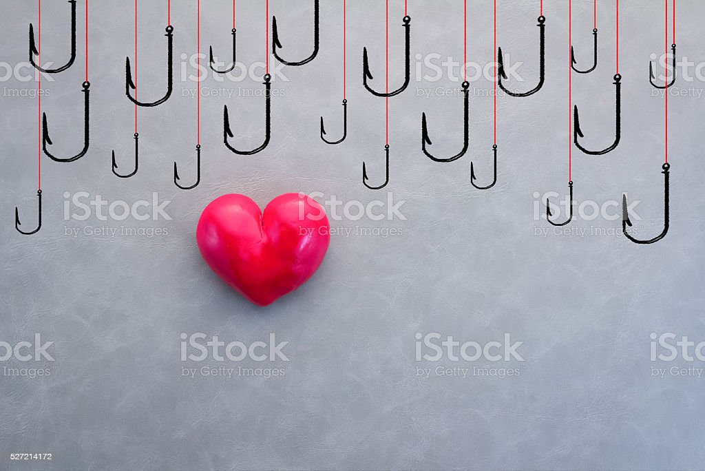 red heart with drawing of hooks stock photo